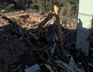 backhoe sitting in shaded section of demolition job site