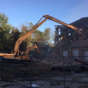 demolition crew demolishing large brick building in central pa