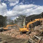 backhoes at work demolishing large brick building