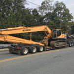 demolition backhoe sitting on large truck parked on street