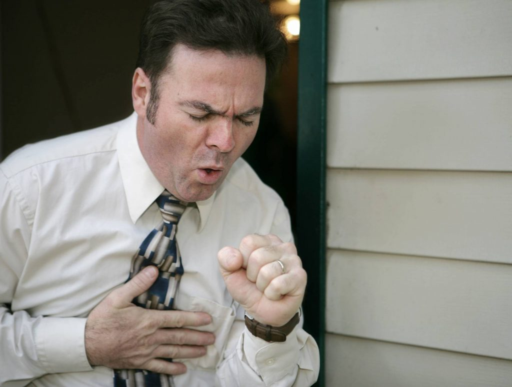 man coughing with symptoms of mesothelioma