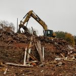 brick building being demolished by demolition crew