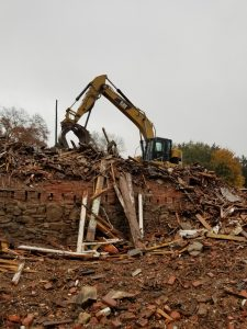 brick building being demolished by demolition crew
