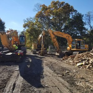 demolition professionals cleaning job site with backhoes