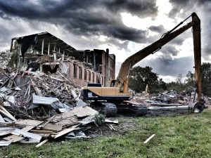 large brick building in the beginning stages of full building demolition