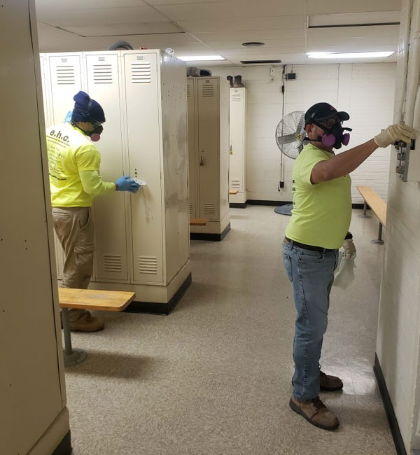 workers cleaning and sanitizing various surfaces in a locker room